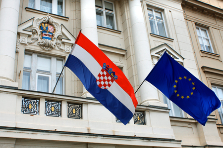 geopolitics: Flags of Croatia and European Union against the facade of Croatian Government building in historic Zagreb