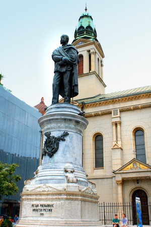 church flower: Monument of Croatian poet Petar Preradovic on Preradovic square (Flower square) and Serbian orthodox church and modern building in the background, Zagreb, Croatia