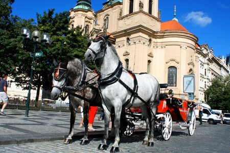 Prague - town square with horses for turistic ride and St. Nicholas? Church on Lesser Town Square. Stock Photo