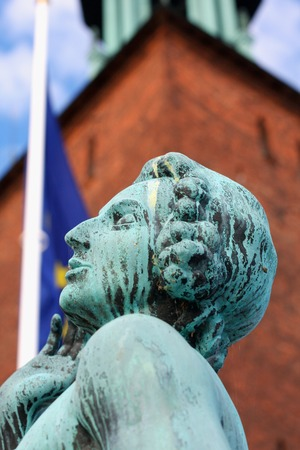 statue on ancient building in Stockholm used as city hall with EU flag on back Stock Photo