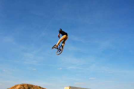 man in sportswear jumping high on mountain bicycle on background of landscape.