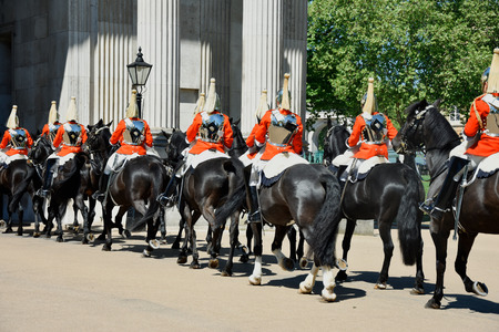 Royal guards on horseback dressed in ceremonial red coats pass in a parade - uk Redakční