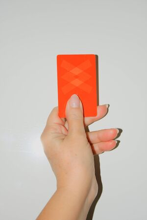 sport, caution, game and people - close up of referee hands with whistle showing red card