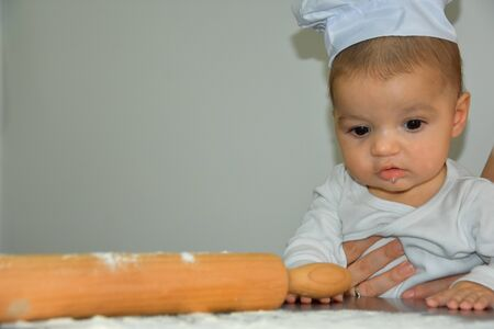 Cute baby boy cooking in kitchen at home