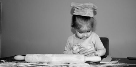 girl decorating Christmas cookies in the kitchen Stock Photo