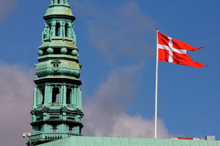 Danish Flag In The Wind next to the church tower in Copenhagen