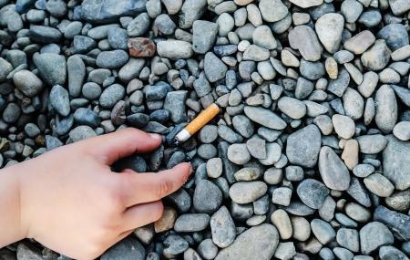 Baby hand raised cigarette butt photo