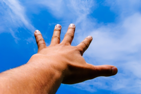 mans hand stretched out against the blue sky