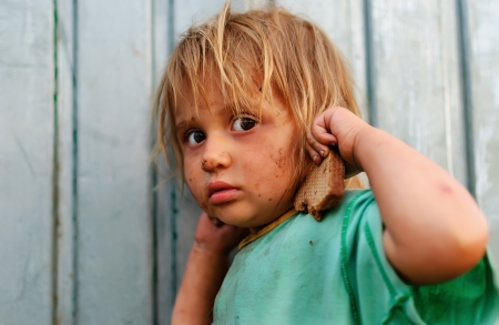 poverty relief: Frightened girl with a piece of bread in his hand, poverty and hunger Stock Photo
