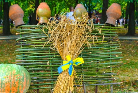 sheaf of wheat and wicker fence with clay pots on it photo