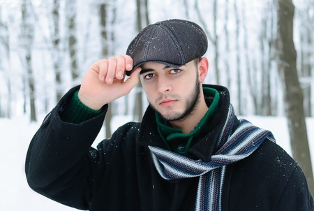 man in black coat and a hat on his head during winter photo