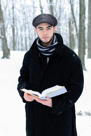 young man in black coat with a book hand photo