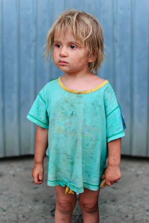 Frightened girl with a piece of bread in his hand, poverty and hunger photo