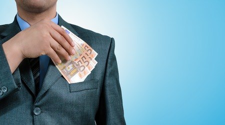 venality: man put the euro in a jacket pocket Stock Photo