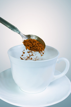 bove: White coffee mug with a teaspoon of granulated instant bove the cup