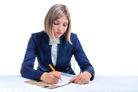 young woman writing in a notebook isolated on white background photo