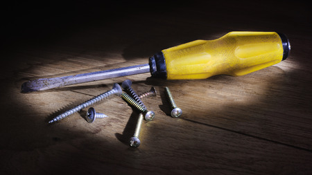 turn the screw: screwdriver with screws on the wooden floor illuminated by the light