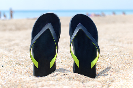 a pair of flip-flops stuck on the sand of a beach Stock Photo