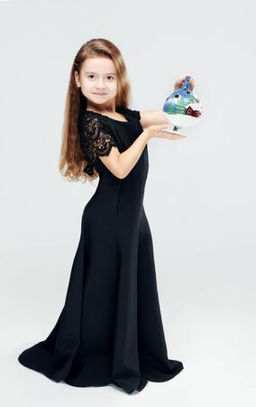 Little girl girl in studio posing in front of the camera in a black dress on a gray background