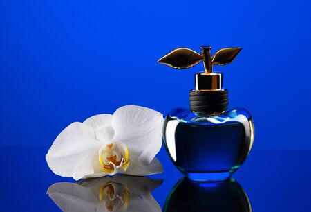 Bottle of expensive perfume shot close-up on a blue background