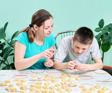 Mom teaches son to sculpt dumplings with cottage cheese in the kitchen.