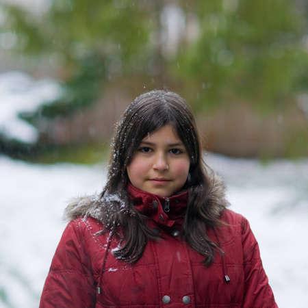 Teen girl standing in light snowfall