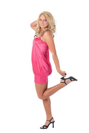 Beautiful blond girl in pink dress standing with one foot raised holding her heel photo
