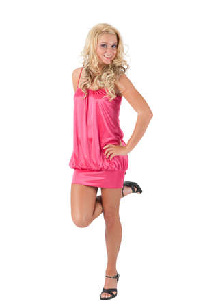 Beautiful blond girl in pink dress standing with one foot raised photo