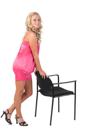 Beautiful blond girl in pink dress leaning on a chair photo