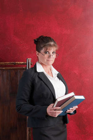 Conservative female teacher holding books photo
