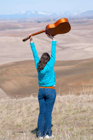 Young girl on a hill throwing guitar in the air photo