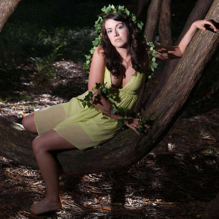 fairy forest: Beautiful girl in green organic makeup sitting on a tree trunk under dramatic light Stock Photo