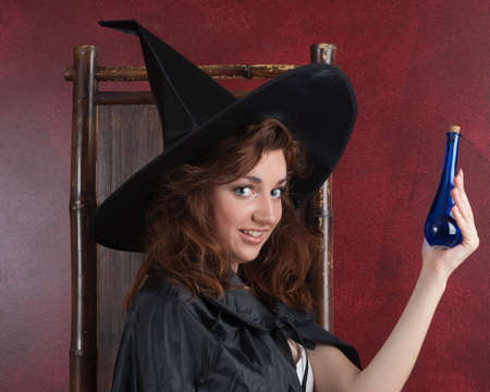 potion: Young girl in witch hat and cape  holding two vials with potions