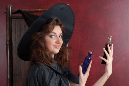 Young girl in witch hat and cape  holding two vials with potions