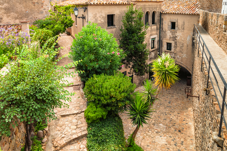 Romantic old street with stairs and plants in Tossa de Mar, Costa Brava, Catalonia, Spain