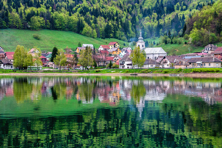 Village called Dedinky with its reflection in Palcmanska Masa reservoir, which is used for water sports recreation and trout fishing in Slovakia. Village is situated on the south of National park Slovak paradise. Fresh spring season theme with many shades