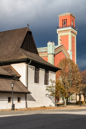 Old Wooden articular church and New red protestant church in Kezmarok, Spis region, Slovakia. Old one is registered in UNESCO List of the World Cultural Heritage. Sunlight with dramatic storm clouds. Stock Photo