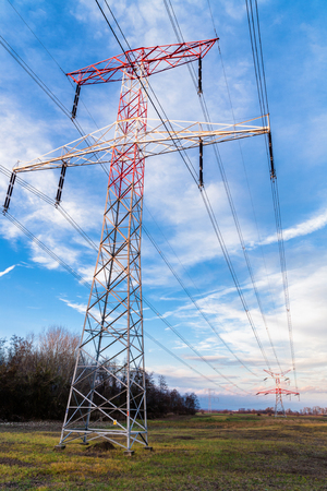 High voltage electric powerlines and pylons with blue sky and some clouds in background. Stock Photo