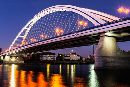 Illuminated Apollo bridge with lights reflection on surface of Danube river at dusk in Bratislava, Slovakia. Travel and engineering  theme.