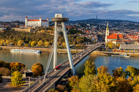 Cityscape of Bratislava with main symbols of the city: castle, SNP bridge over Danube river, St.Martin´s church and broadcast tower in background. Warm sunset light.