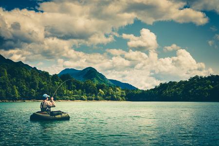 bellyboat에 앉아 제 니스 니, 슬로베니아에서 호수에 큰 송어와 함께 싸우는 어 부. 아직도 물 플라이 낚시 및 야외 라이프 스타일 테마. 변덕스럽고 대조