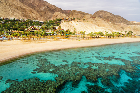 Coral reef of Aqaba Bay in Red Sea, empty beach and desert near Eilat, Israel. Contrast between turqoise coral sea and dry desert. Travel theme.