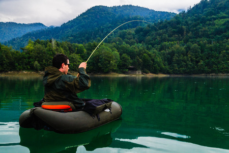 Fisherman fighting with big trout while floating with bellyboat on lake in Jesenice, Slovenia. Cloudy day after rain.