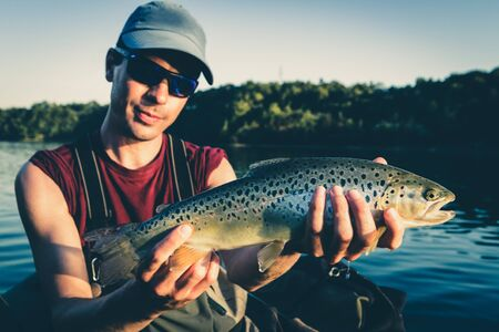 Visser met vangst van grote bruine forel op meer in Jesenice, Slovenië. Zonnige zomerdag. Still water vliegvissen en outdoor lifestyle thema. Stockfoto