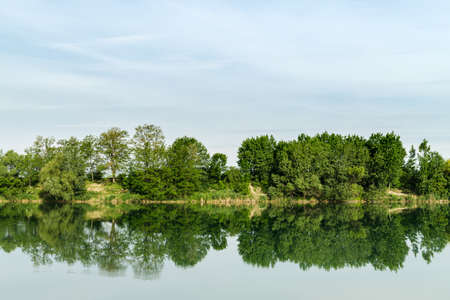 Reflection of green trees in water surface of lake called Zelena voda in Slovakia.
