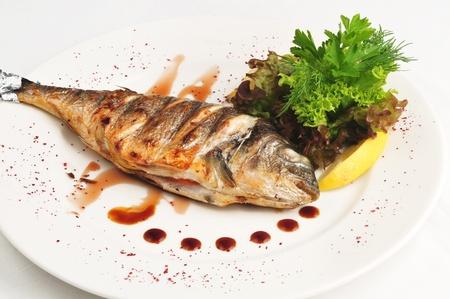 Die gebratenen Fisch mit So?e und Salat auf einem wei?en Teller