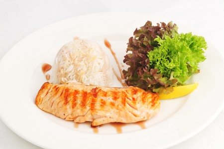 Fried salmon with rice and salad on a white plate photo