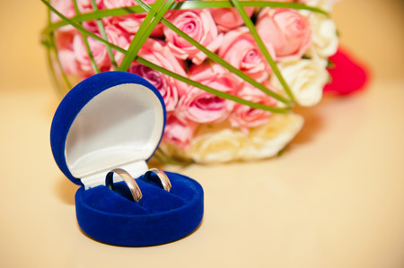 wedding rings in the blue box on the background of the brides bouquet of pink and white roses photo