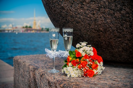 a glass of champagne and a bouquet of the bride photo