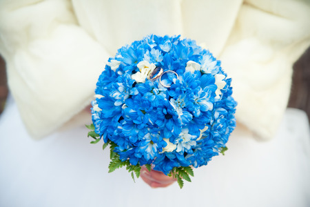 fur coat: Bride in a fur coat holding a bouquet of blue and white flowers which lie wedding rings Stock Photo